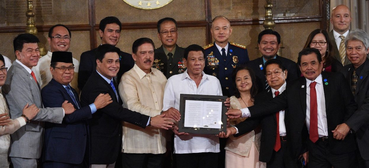 Philippine President Rodrigo Duterte (C) poses for photos during the presentation of the signed document on the Organic Law for Bangsamoro Autonomous Region of Muslim Mindanao to the Moro Islamic Liberation Front (MILF) during a ceremony at Malacanang palace in Manila on 6 August, 2018. (Photo: Ted ALJIBE/ AFP)