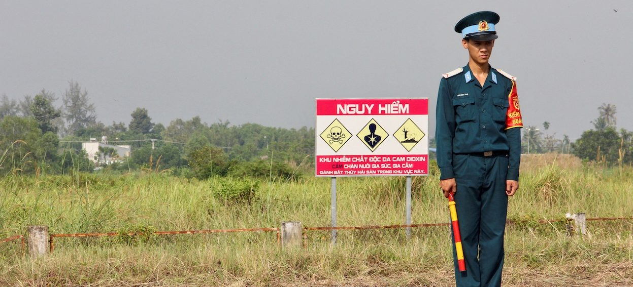 A Vietnamese soldier stands next to a hazardous warning sign by a runway at Bien Hoa air base, on the outskirts of Ho Chi Minh City, as US Defence Secretary Jim Mattis visits the former US air base on 17 October, 2018. (Photo: Thomas WATKINS/ AFP)