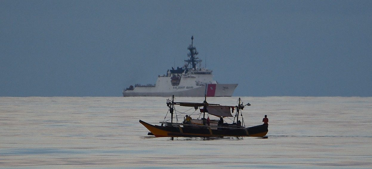 Filipino fishermen aboard their boat sails past US coastguard ship Bertholf during a joint exercise between Philippine and US coastguards joint near Scarborough shoal in the South China Sea on 14 May, 2019. (Photo: Ted ALJIBE / AFP)