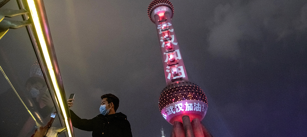 A man takes a selfie in front of the Oriental Pearl Tower in Shanghai