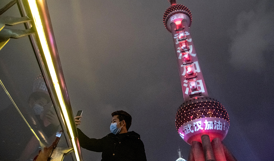 A man takes a selfie in front of the Oriental Pearl Tower