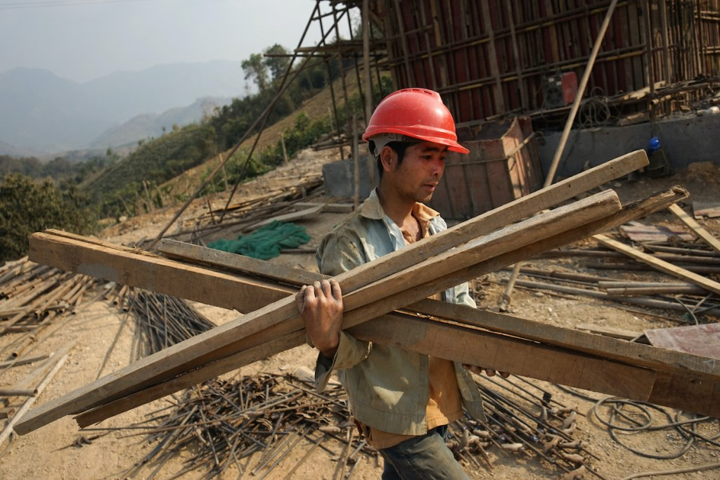 """A Chinese worker carrying materials for the first rail line linking China to Laos, a key part of Beijing's """"Belt and Road"""" project across the Mekong, in Luang Prabang on 8 February, 2020. (Photo: Aidan JONES/ AFP)"""