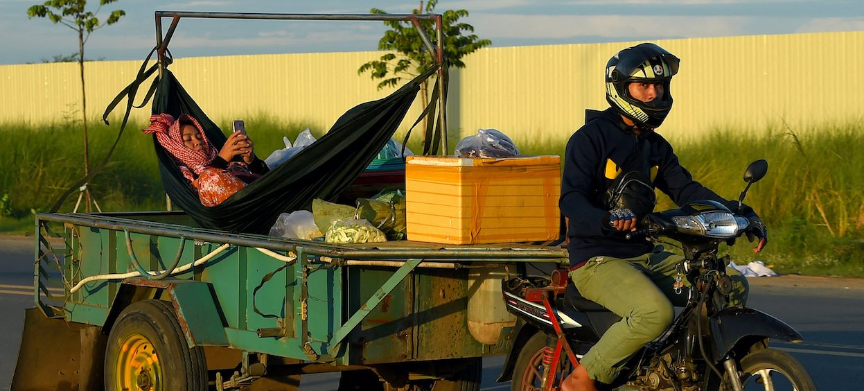 A man rides a motorbike pulling a trailer with a woman relaxing in a hammock, checking her phone, on a street in Phnom Penh on 12 June, 2020. (Photo: TANG CHHIN Sothy/ AFP)