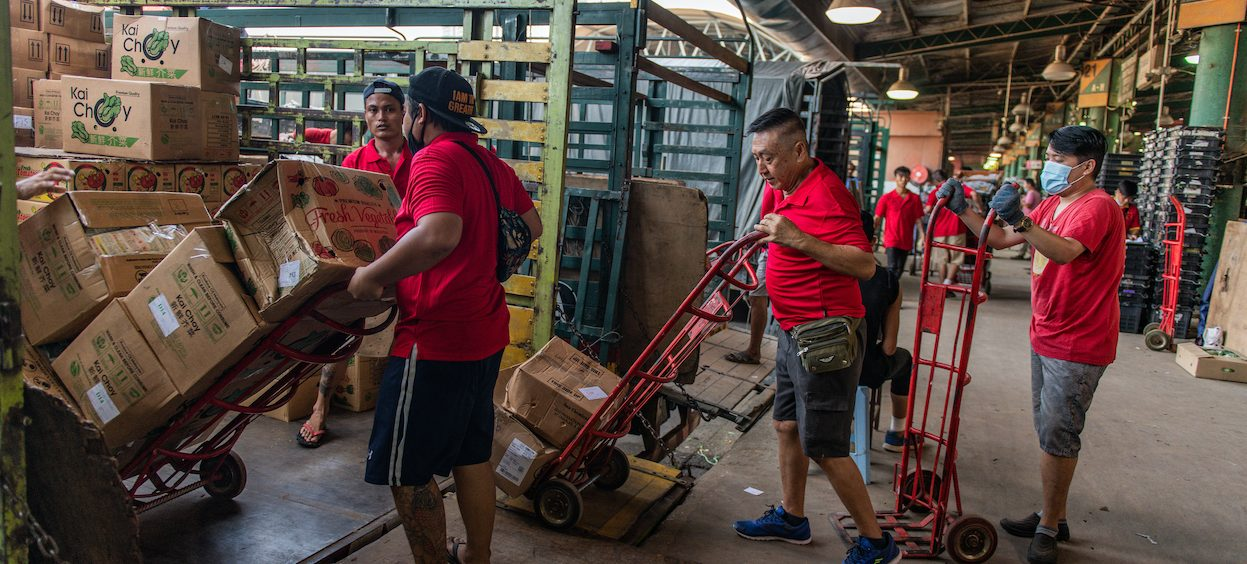 Workers push boxes of vegetables for sale at a wholesale market in Kuala Lumpur on 15 June, 2020, as sectors of the economy are being reopened following restrictions to halt the spread of the Covid-19 coronavirus. (Photo: Mohd RASFAN/ AFP)