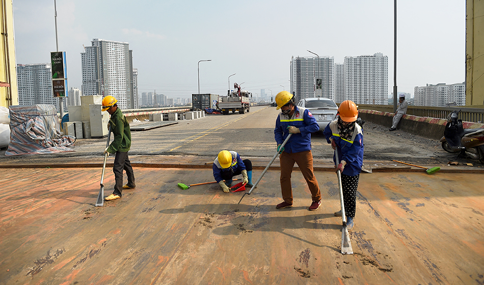 workers clean the surface of Thang Long bridge