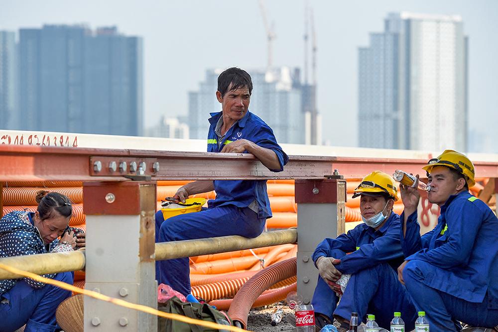 Workers take a break on Thang Long bridge in Hanoi.