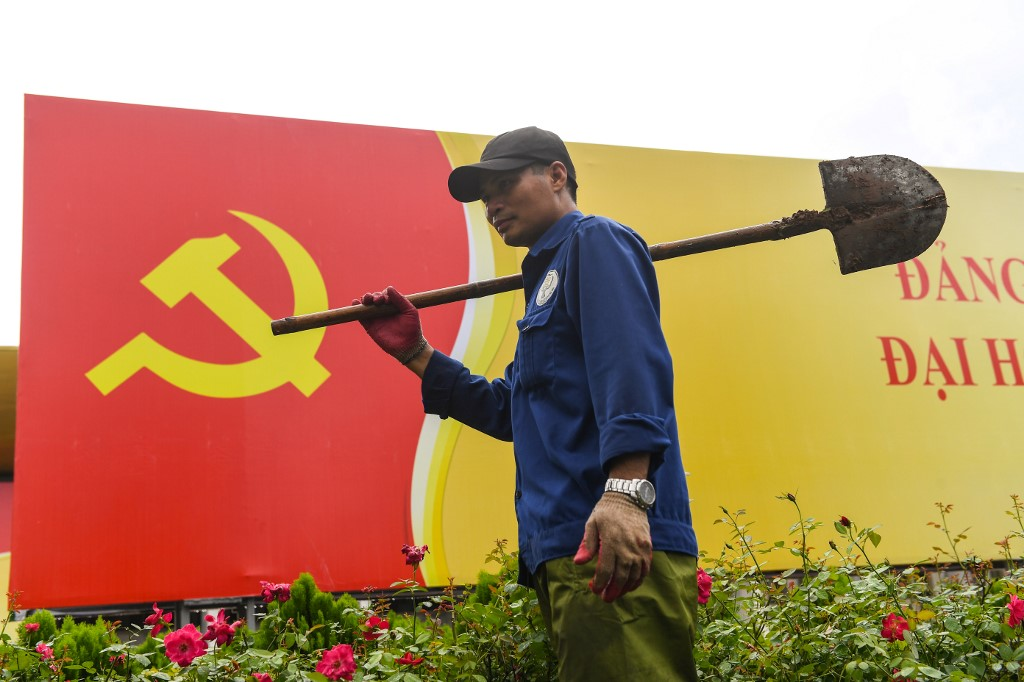 A worker walks past a signboard with the Communist Party flag in Hanoi