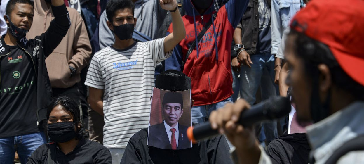 Students cover their faces with Indonesian President Joko Widodo during a demonstration against a controversial new law passed last week which critics fear will favour investors at the expense of labour rights and the environment in Banda Aceh on October 14, 2020. (Photo by Chaideer MAHYUDDIN/ AFP)