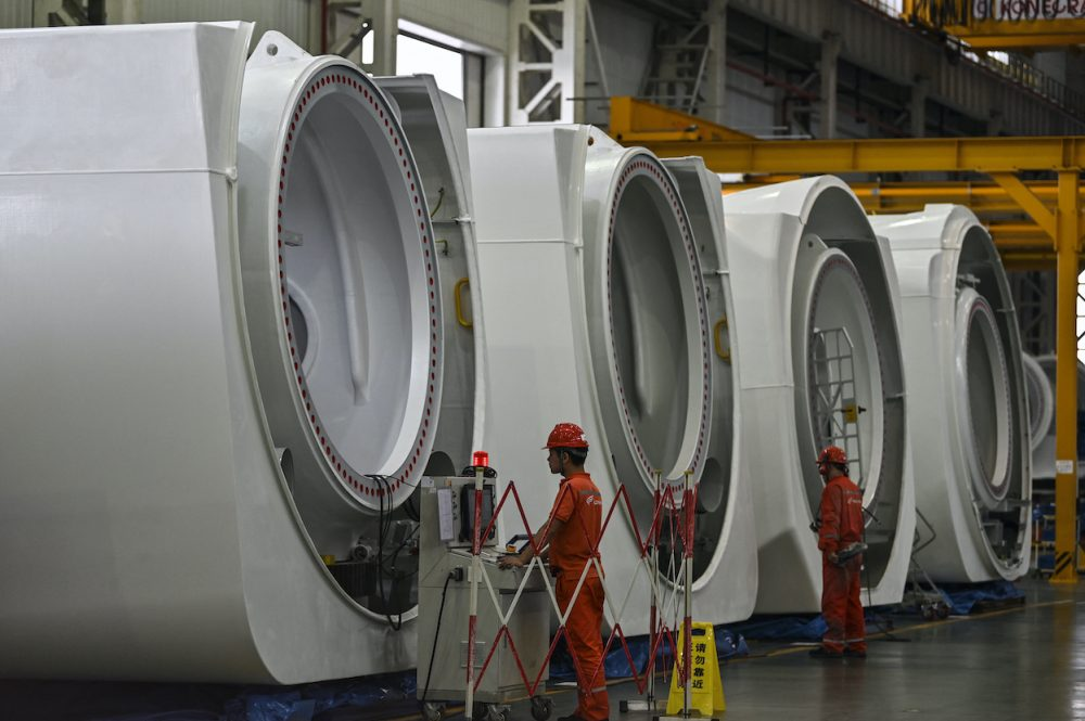 Workers are seen during the production process of wind turbines during a government organised tour at Goldwind Technology in Yancheng, in Jiangsu province on 14 October, 2020. (Photo: Hector RETAMAL/ AFP)
