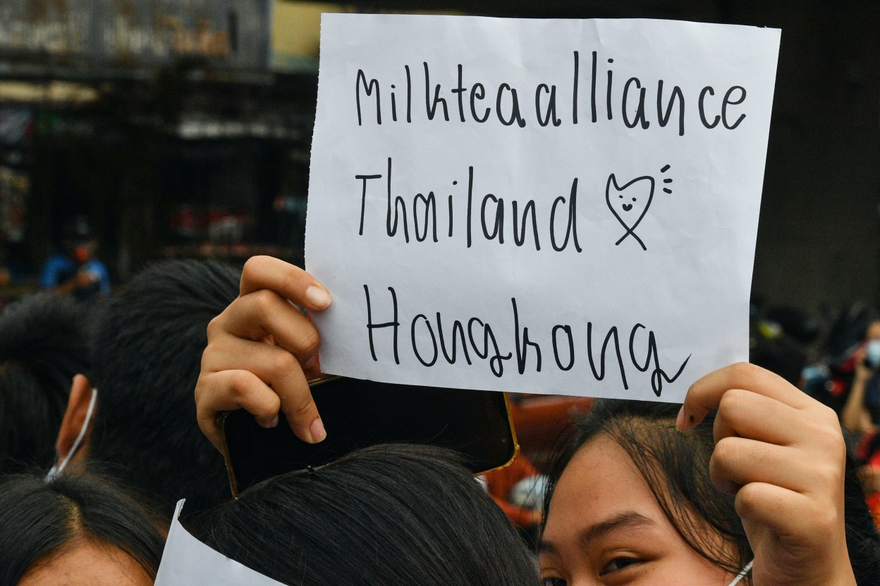 """A pro-democracy protester holds up a sign relating to the """"milk tea alliance"""" during an anti-government rally at Kaset intersection in Bangkok on October 19, 2020."""