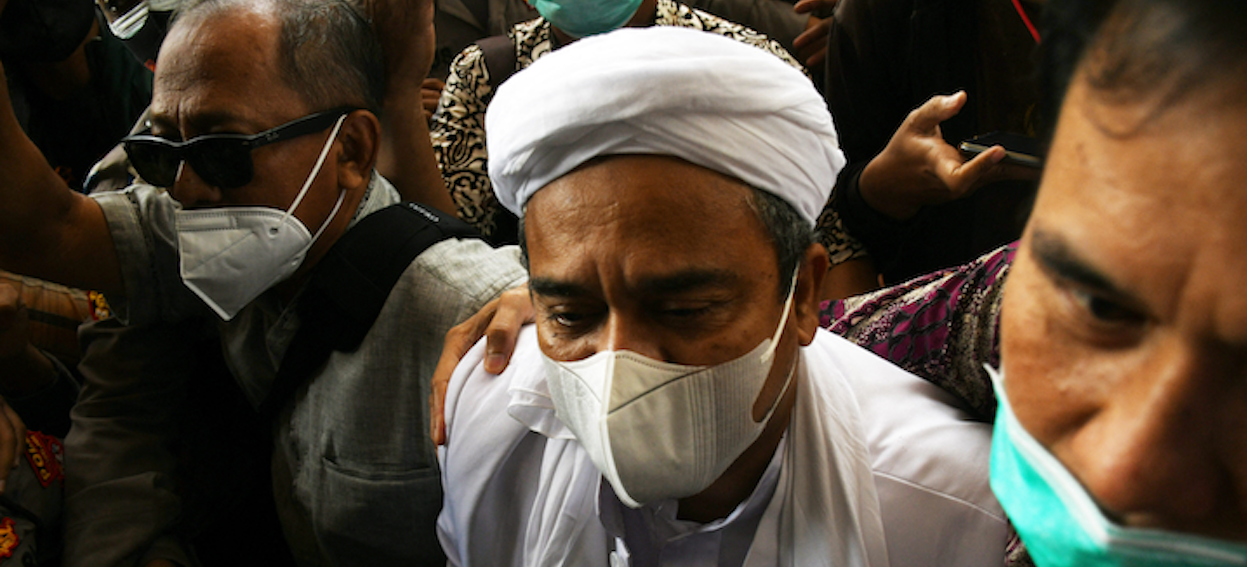 Indonesian Muslim cleric Rizieq Shihab (C), founder and leader of Front Pembela Islam (FPI), surrounded by his supporters on arrival at the police headquarters in Jakarta on 12 December, 2020. The effect of Telegram suppressing jihadi channels and the Indonesian government clamping down on opposition Islamist groups and driving them into the virtual sphere has created fertile ground for crosspollination between pro-ISIS and pro-FPI militants. (Photo: Dasril ROSZANDI/ AFP)