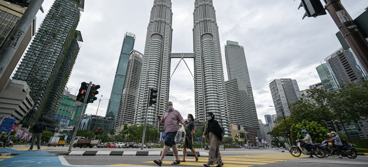Pedestrians cross a road in front of Malaysia's landmark Petronas Twin Towers in Kuala Lumpur on 12 January 2021, as Malaysian authorities were set to impose tighter restrictions to try to halt the spread of the Covid-19 coronavirus. (Photo: Mohd RASFAN/ AFP)
