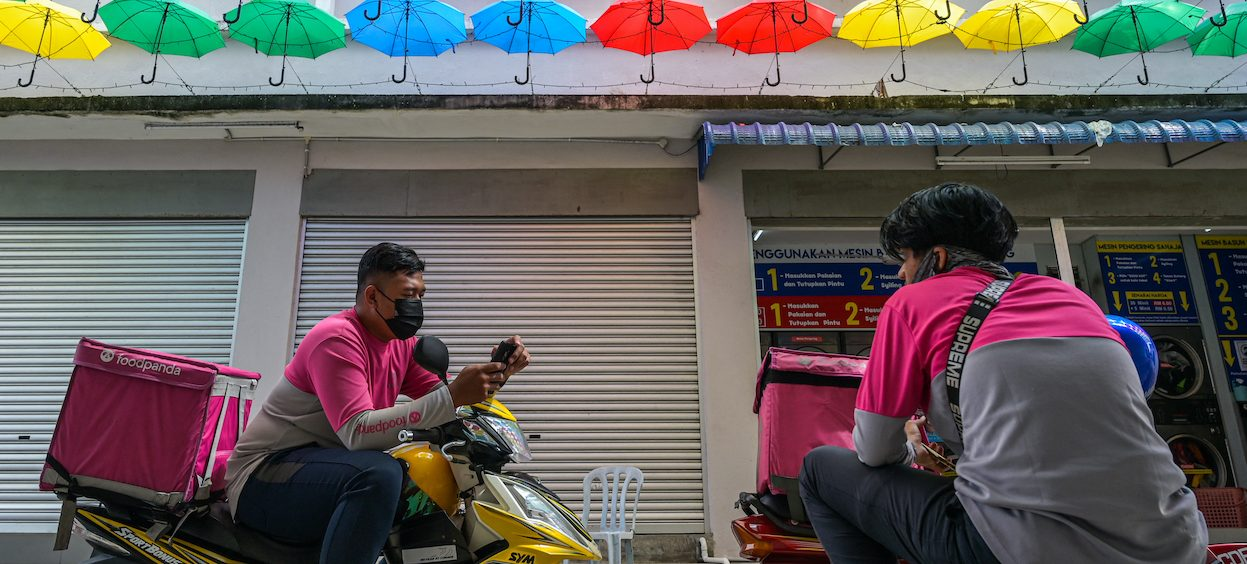 Two foodpanda delivery motorcycle riders wait for orders in Mentakab in Malaysia's Pahang state on 19 January, 2021. The government needs to provide greater support for the self-employed and informal economy as Malaysia moves towards a phase of economic recovery. (Photo: Mohd RASFAN/ AFP)