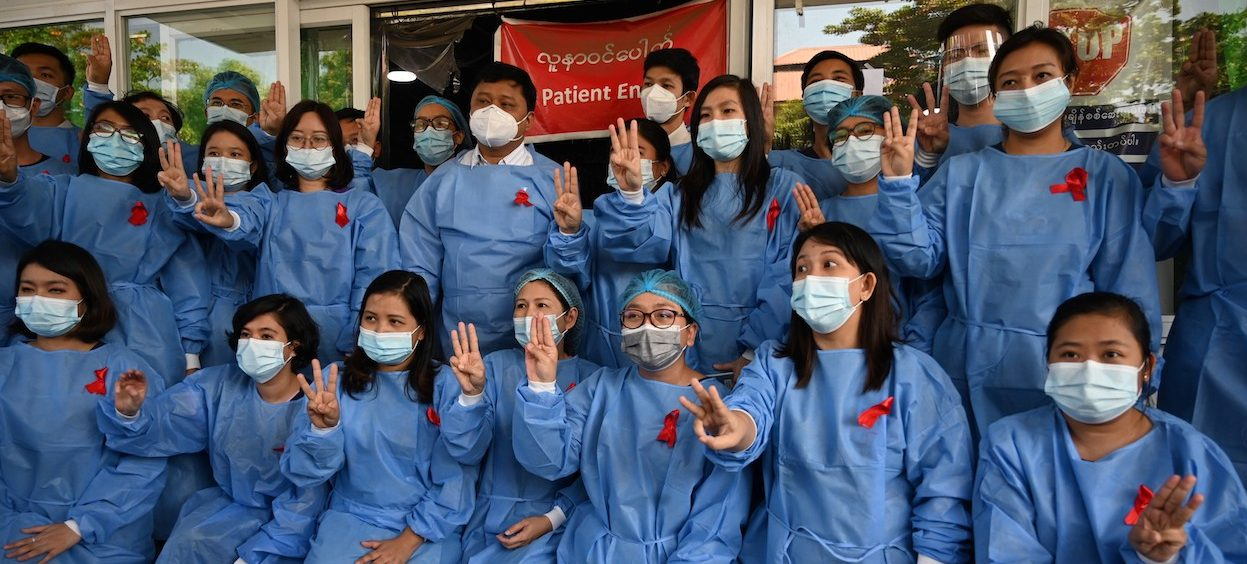 Medical staff make a three finger salute with red ribbons on their uniforms at the Yangon General Hospital in Yangon on February 3, 2021 as calls for a civil disobedience gather pace following a military coup detaining civilian leader Aung San Suu Kyi. (Photo: STR/ AFP)