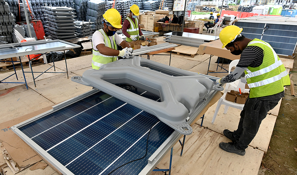 workers fixing a floater onto a solar panel as part of the construction of a floating solar power farm on Tengeh reservoir in Singapore
