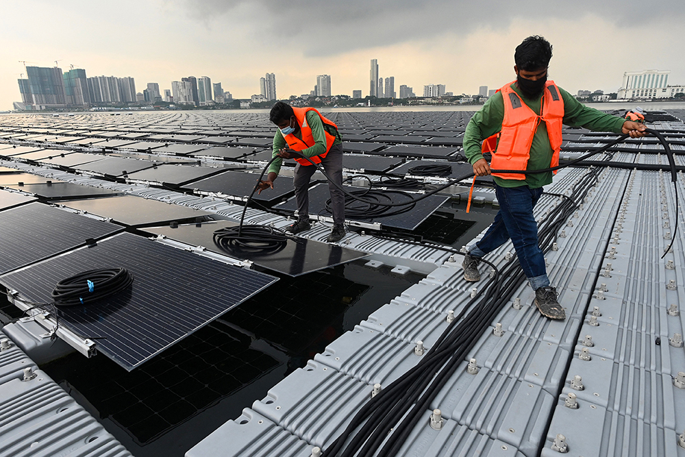 Workers laying cables on a floating solar power farm at sea
