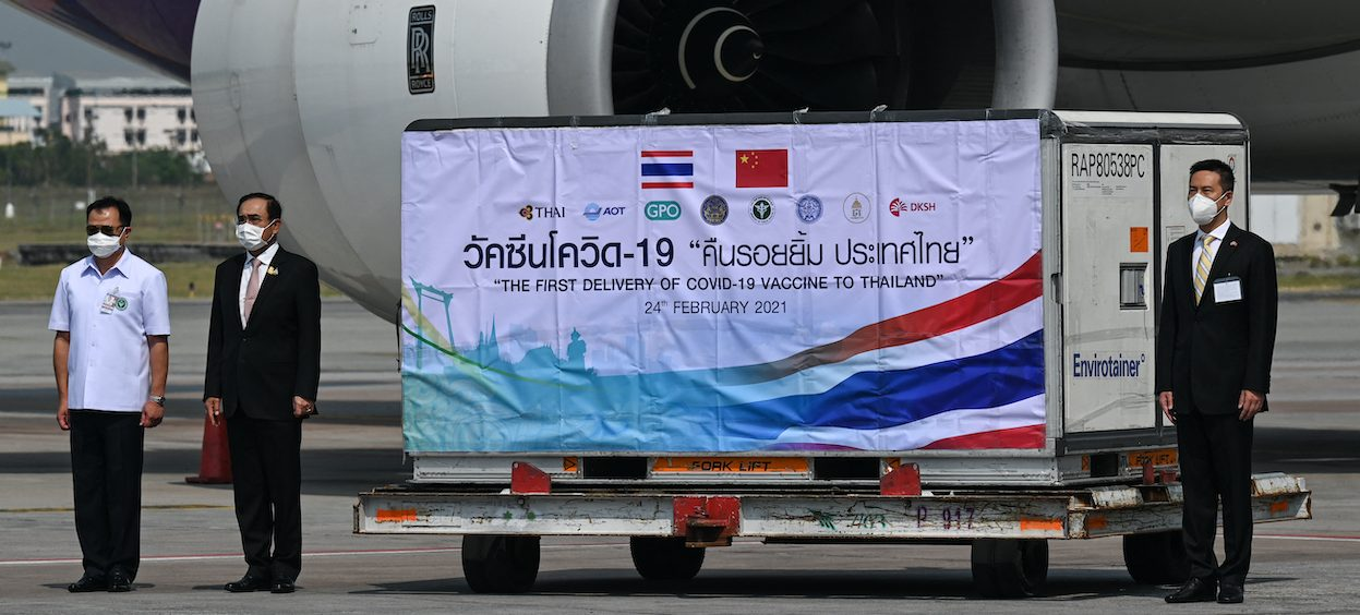 Thailand's Prime Minister Prayut Chan-O-Cha (C), Health Minister Anutin Charnvirakul (L) and Yang Xin, ChargÈ d'Affaires of the Chinese embassy, stand beside a shipment of the CoronaVac Covid-19 vaccine, developed by China's Sinovac firm, after it arrived in Bangkok on 24 February, 2021. (Photo: Lillian SUWANRUMPHA/ AFP)