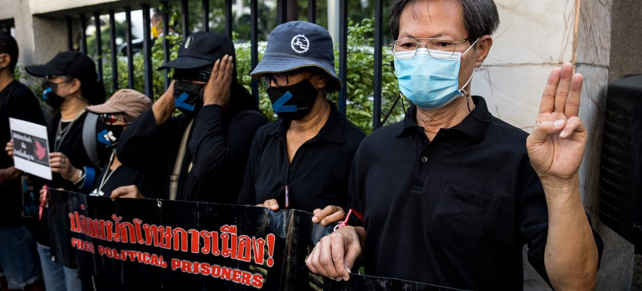 Protesters display banners outside the Criminal Court in Bangkok on 24 February, 2021, during a demonstration calling for the release of pro-democracy activists held under Thailand's lese-majeste royal defamation laws. (Photo: Jack TAYLOR/ AFP)