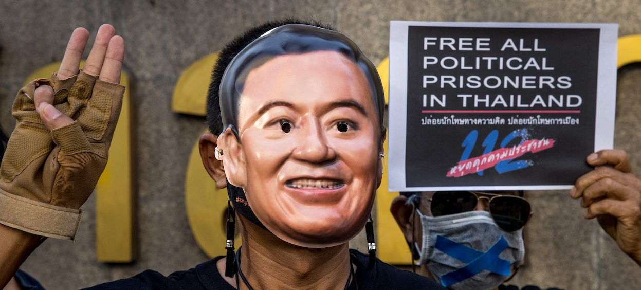 A protester wearing a mask of former Thai prime minister Thaksin Shinawatra during a demonstration on 24 February, 2021, which called for the release of pro-democracy activists held under Thailand's lèse majesté royal defamation laws. Thaksin has recently used the Clubhouse application to communicate with his followers. (Photo: Jack TAYLOR/ AFP)