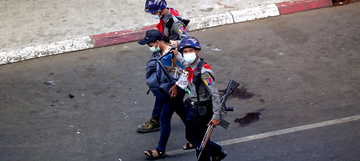 Police arresting a Myanmar Now journalist in Yangon