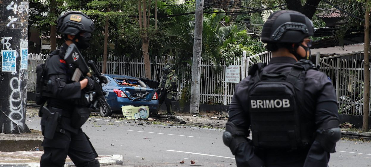 An Indonesian anti-bomb unit (C) collects evidence as anti-terror police from Brigade Mobile (black uniform) stand by after a bomb exploded in Makassar on 28 March, 2021. (Photo: Irvan ABDULLAH/ AFP)