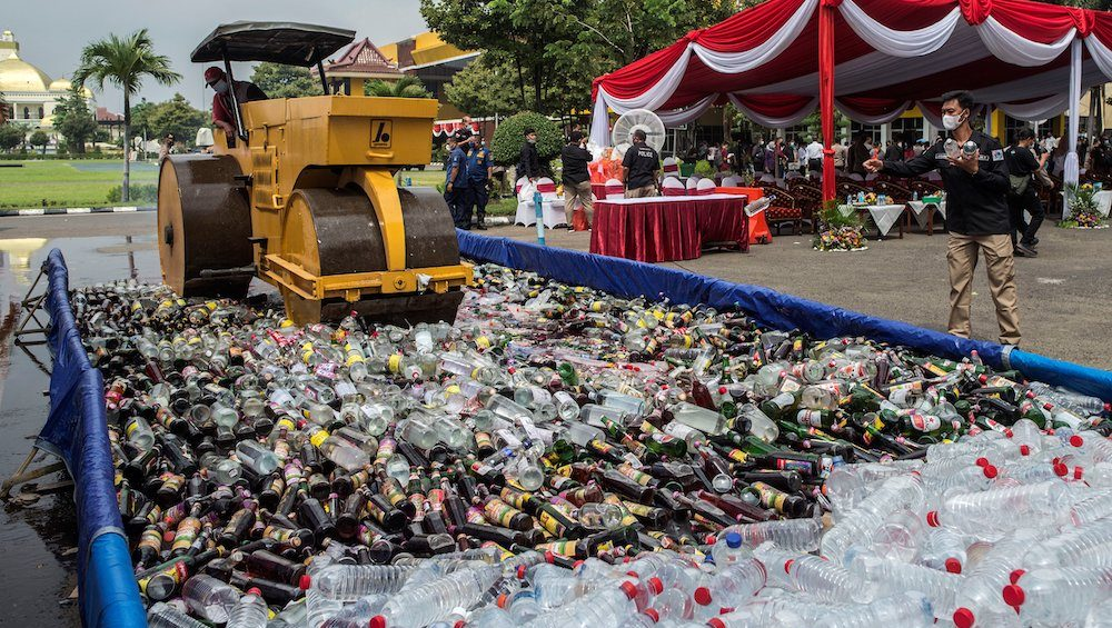 Indonesian authorities destroy thousands of bottles of alcohol during a ceremony at the police headquarters in Surabaya on 12 April, 2021, ahead of Islam's holy month of Ramadan. (Photo: Juni KRISWANTO / AFP)
