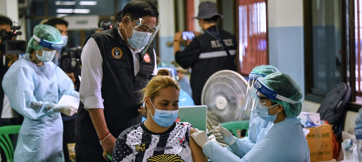 In this picture, Bangkok Governor Aswin Kwanmuang watches as a medical staff member injects a dose of the CoronaVac vaccine, developed by China's Sinovac, into the arm of a woman from the Klong Toey community at a school on 4 May, 2021. The election for the post of governor of Bangkok is planned to take place in the last quarter of this year. (Photo: Lillian SUWANRUMPHA/ AFP)