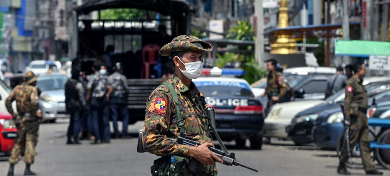 A soldier stands guard along a road as security forces search for protesters, who had been taking part in a demonstration against the military coup, in Yangon on 7 May, 2021. (Photo: STR/ AFP)