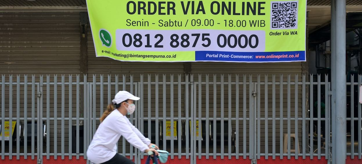 The Covid-19 pandemic has benefited the fintech sector in Indonesia, with more people going online to socialize, work, study and do their shopping. In this picture taken on 3 July 2021, a woman cycles past a banner on a shopfront alerting customers that it is only open for online services in Jakarta, as Indonesia imposed a partial lockdown in the capital due to the COVID-19 coronavirus Delta variant. (Photo: Bay ISMOYO/ AFP)