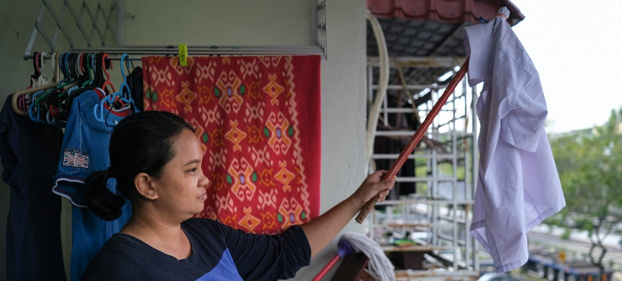 A single mother Tilda Kalaivani waving a white shirt to use as a white flag to call for help after being affected by the Covid-19 pandemic, in her rental apartment in Kuala Lumpur on 6 July, 2021. (Photo: Mohd RASFAN/ AFP)