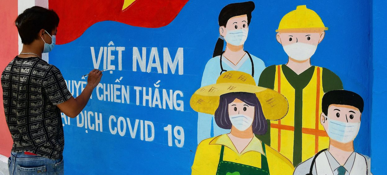 A street artist paints a mural depicting Covid-19 coronavirus frontline workers along a street in Hanoi on 15 June, 2021. (Photo: Nhac NGUYEN/ AFP)