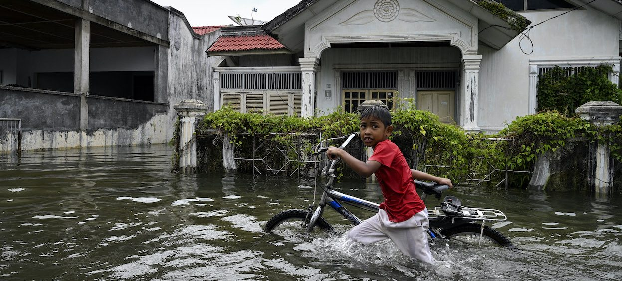A child pushes his bike through floodwaters following heavy rain at a residential area of Ajun on the outskirts of Banda Aceh on 11 August, 2021. (Photo: Chaideer MAHYUDDIN/ AFP)