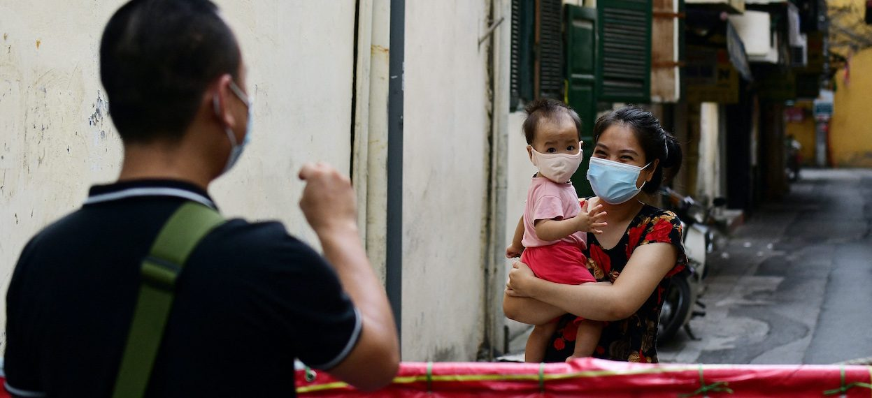 A man talks with his wife and daughter from behind a barricade inside a blocked neighborhood in Hanoi on 24 August, 2021 during the government-imposed lockdown to stop the spread of the Covid-19 coronavirus. (Photo: Nhac NGUYEN/ AFP)