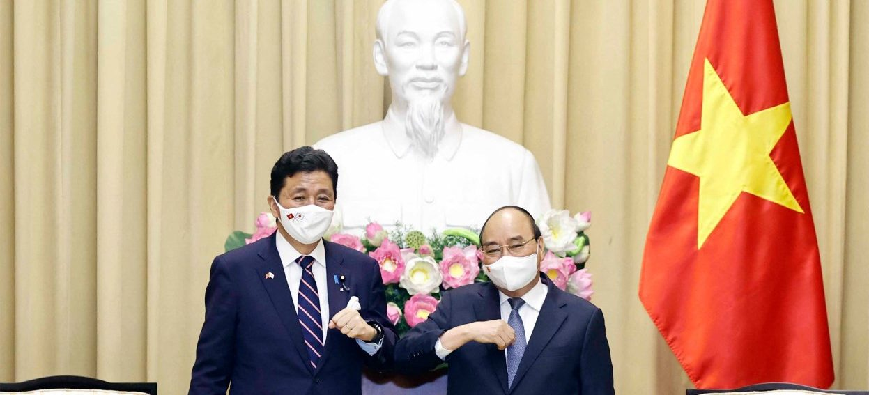 This picture taken and released by the Vietnam News Agency on 12 September, 2021 shows Vietnam's President Nguyen Xuan Phuc (R) bumping elbows to greet Japan's Defence Minister Nobuo Kishi during a meeting in Hanoi. (Photo: ATR/ Vietnam News Agency/ AFP)