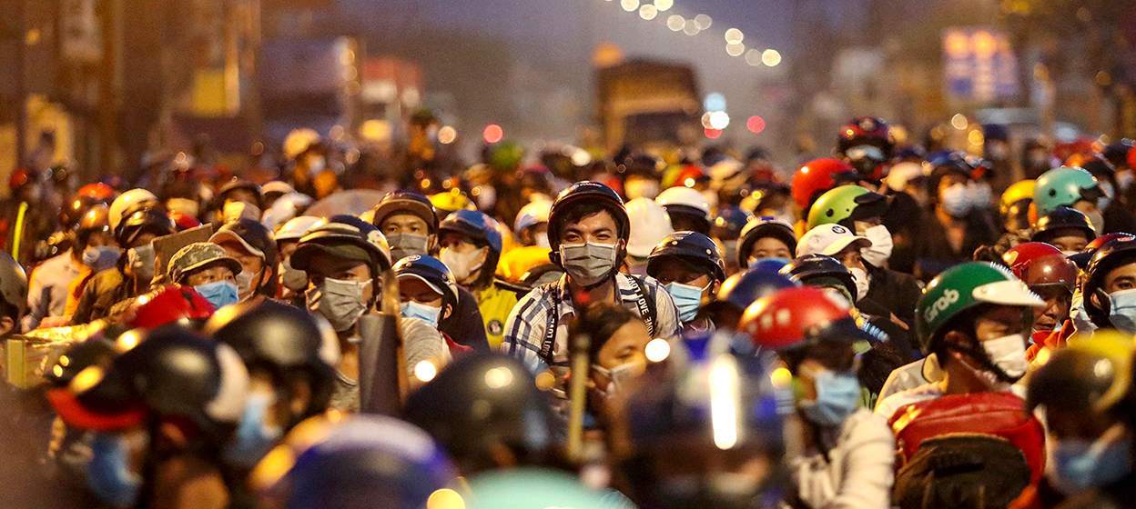 People planning to return to their hometowns wait at a checkpoint to leave Ho Chi Minh City
