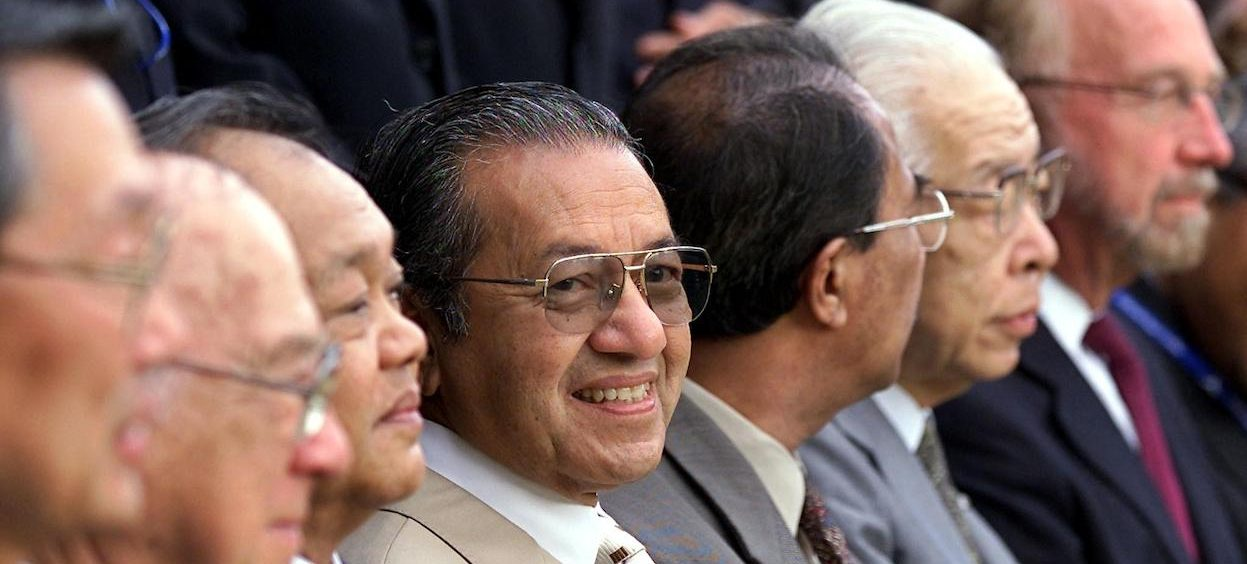 Then Malaysian Prime Minister Mahathir Mohamad (C) smiles during a photo session with IAP members at 6th Multimedia Super Corridor (MSC) International Advisory Panel meeting in Cyberjaya, on the outskirts of Kuala Lumpur, on 5 September, 2002. (Photo: Ahmad YUSNI/ AFP)