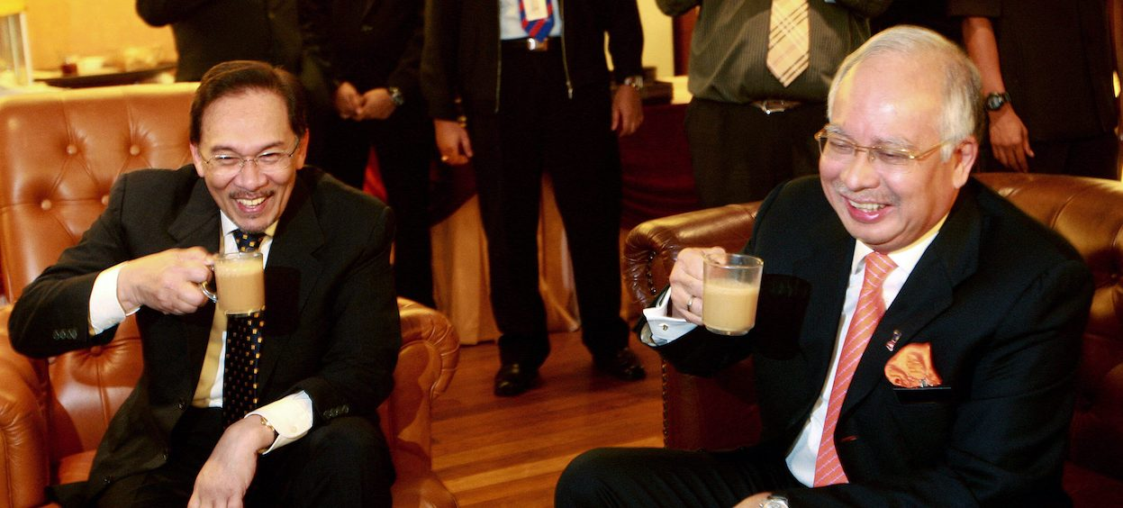 Former Malaysian Prime Minister Najib Razak (R) smiling with opposition leader Anwar Ibrahim (L) as the two enjoy a cup of tea together in the parliament lobby on the sidelines of a session in Kuala Lumpur on 17 November, 2009. Anwar has recently been in talks with UMNO for a possible alliance. (Photo: STR/ AFP)