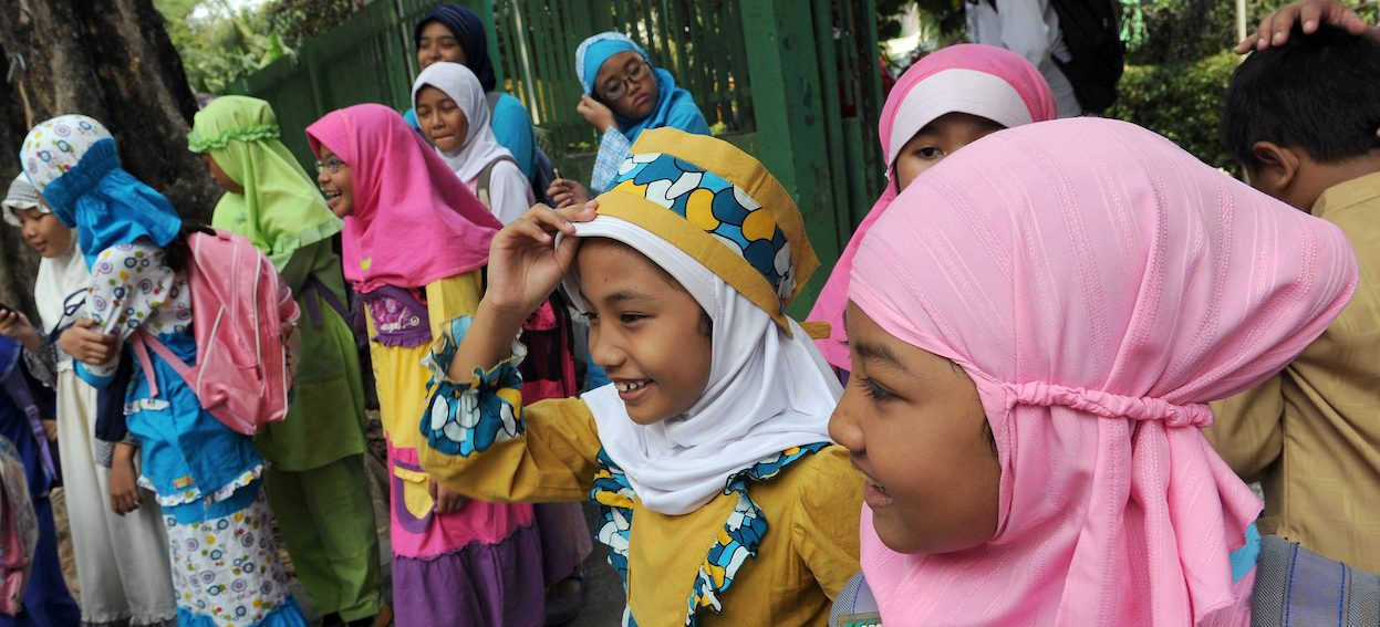 Indonesian public elementary school students leave school at the end of their classes in Jakarta on 1 August, 2012. Children in Indonesia, the worlds most populous Muslim country, wear traditional colorful clothes instead of regular uniforms during the fasting month of Ramadan and focus more on religious studies. (Photo: Romeo GACAD/ AFP)