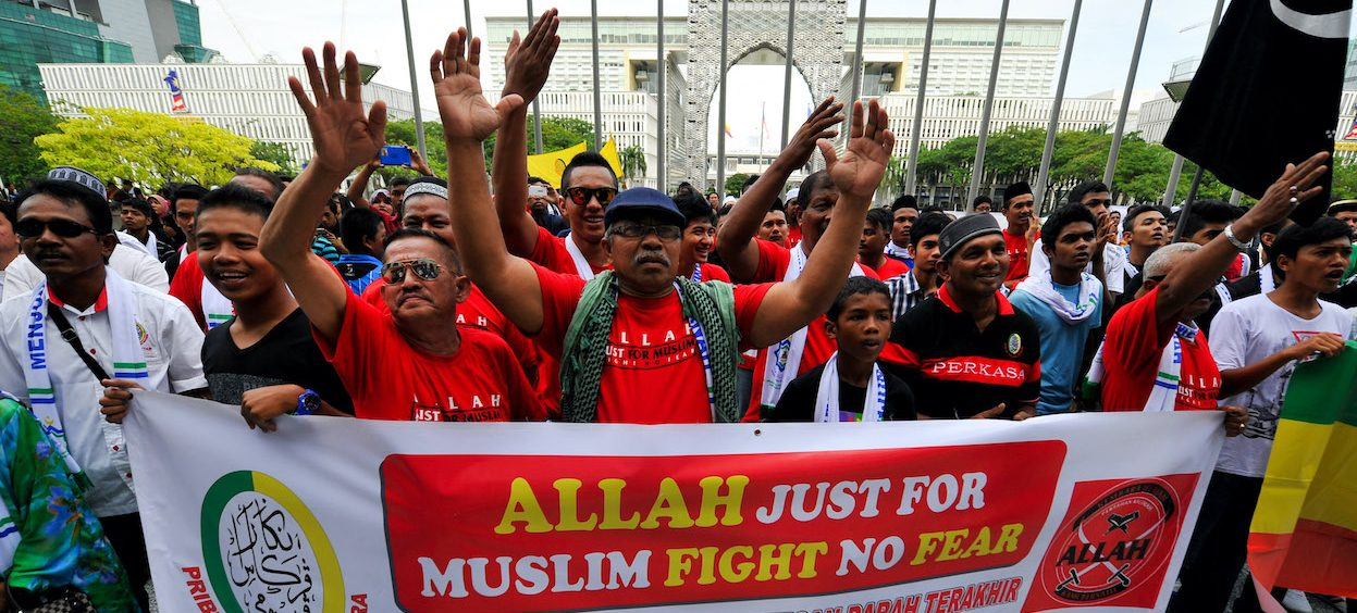 """Muslim Protestors display a banner during a demonstration against a Malaysian Catholic newspaper using the word """"Allah"""" at the court of appeal in Putrajaya, outside Kuala Lumpur on 14 October, 2013. A recent High Court ruling has permitted non-Muslims to use of four previously-prohibited words, including the word """"Allah."""" (Photo: Mohd RASFAN/ AFP)"""