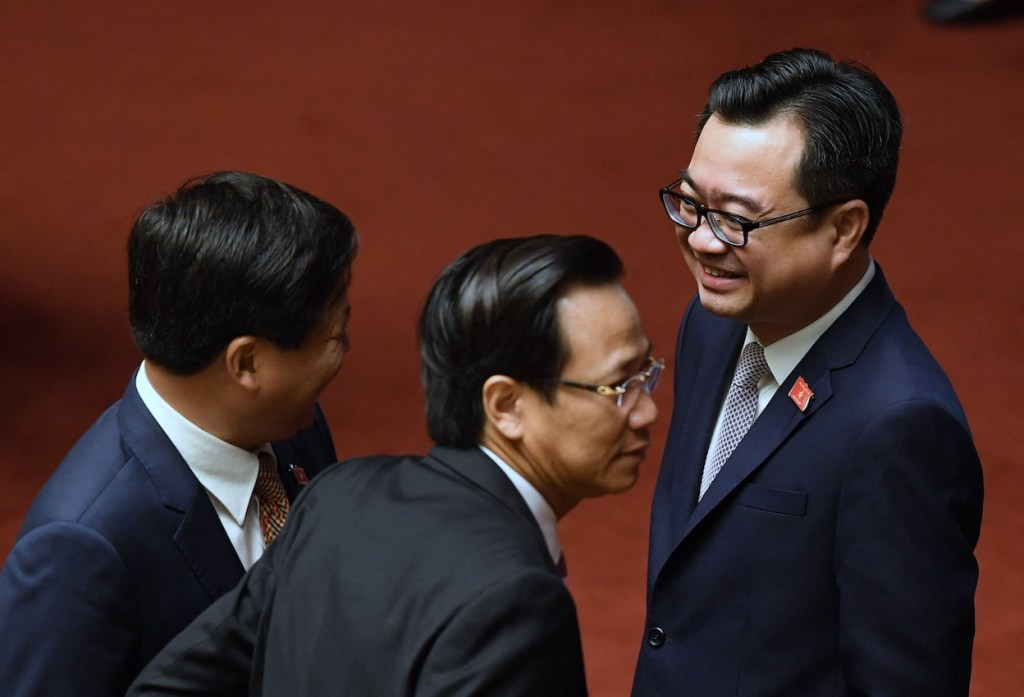 Nguyen Thanh Nghi (R), son of Vietnam's former Prime Minister Nguyen Tan Dung, chats with delegates prior to the opening of the second annual session of the National Assembly in Hanoi on October 23, 2017. Nguyen, who is now the Construction Minister, is the youngest minister in the Cabinet. (Photo by Hoang Dinh NAM/ AFP)