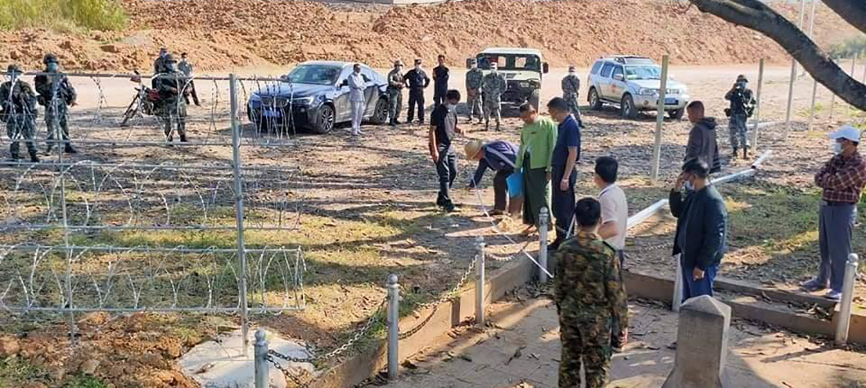 Myanmar and Chinese officials inspect the disputed fence