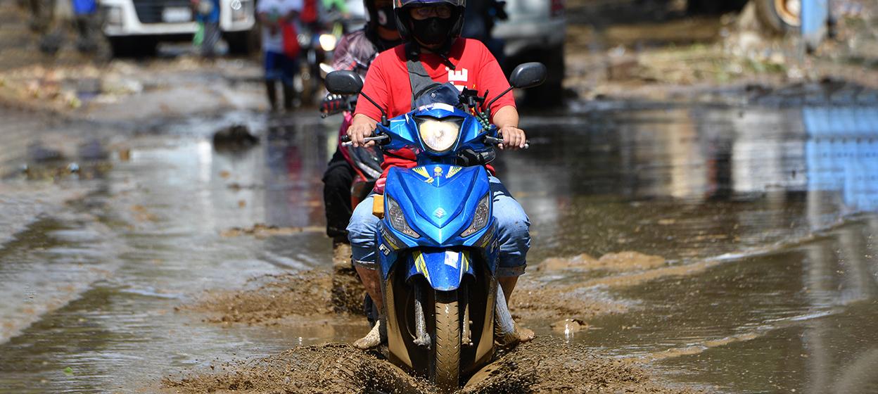 A motorcyclist rides through a muddy street in Marikina City, suburban Manila