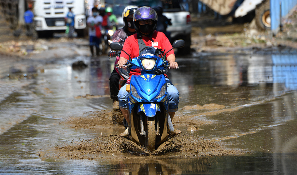 A motorcyclist rides through a muddy street in Marikina City, suburban Manila, on November 13, 2020, a day after Typhoon Vamco hit the capital area bringing heavy rains and flooding. (Photo: Ted Aljibe, AFP)