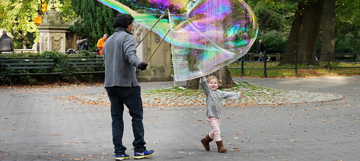 A child reaches for a giant bubble in Central Park