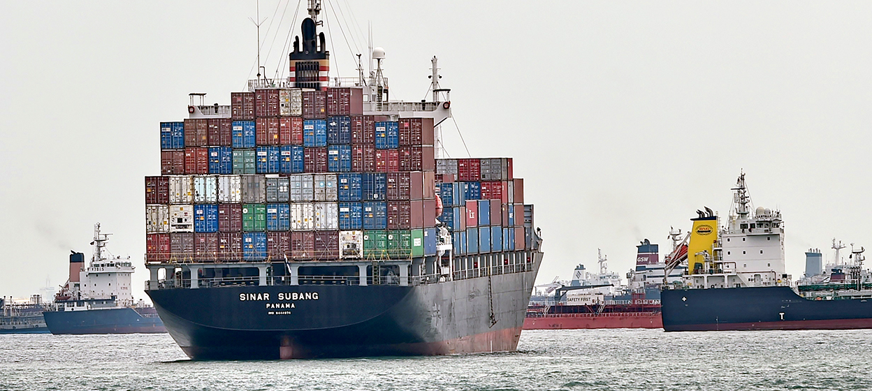 A fully loaded container vessel waits outside a container terminal in Singapore