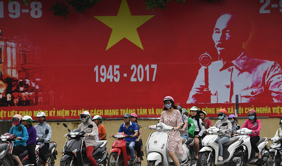 Motorcyclists ride past a poster with a portrait of the late president Ho Chi Minh