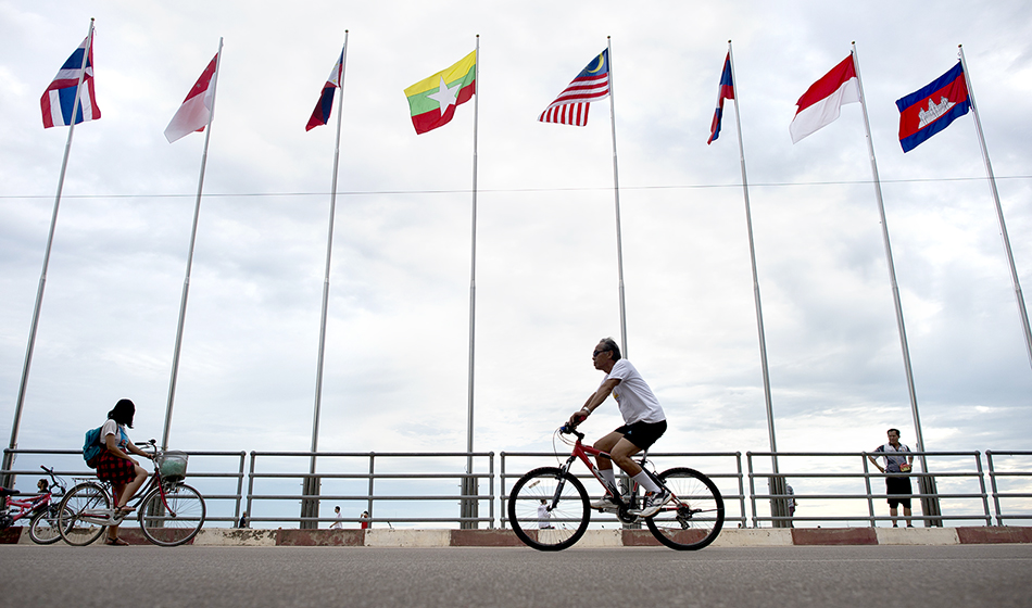 People pass by flags of ASEAN countries along the banks of the Mekong River in Vientiane