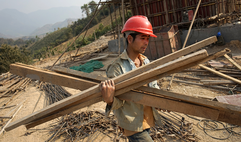 A Chinese worker carries materials for the first rail line linking China to Laos
