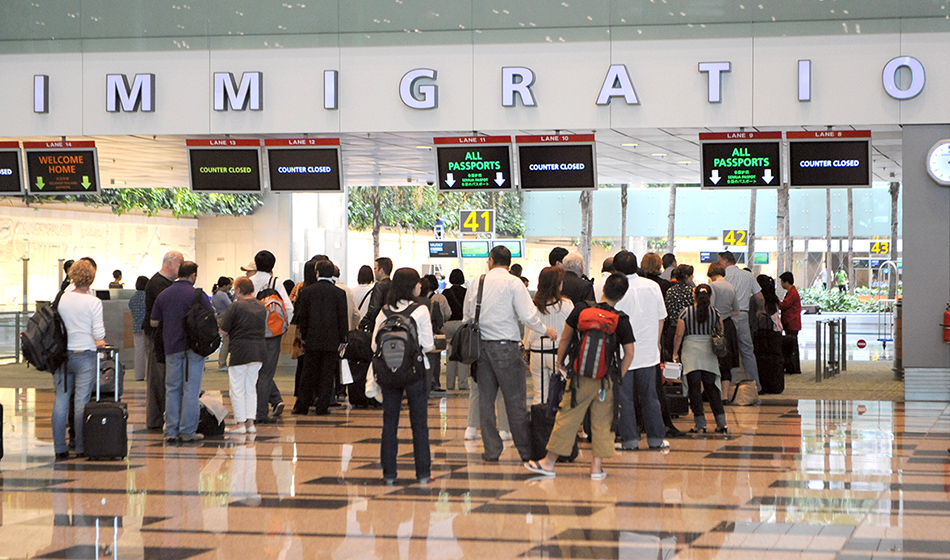 Visitors queuing at the immigration counter after passing through health screening at the Changi