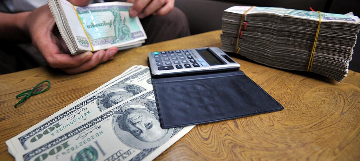 An illegal money changer exchanges Myanmar kyat bank notes into US dollars